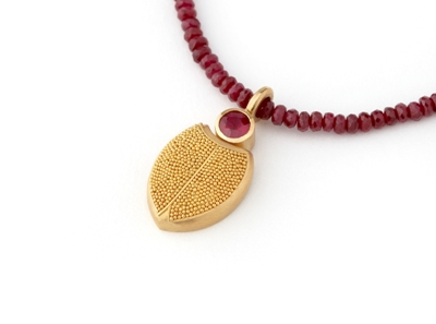 This stunning gold scarab pendant by Pura Ferreiro is crafted using Pura's signature granulation technique and beautifully accented with a striking red ruby. Pi...